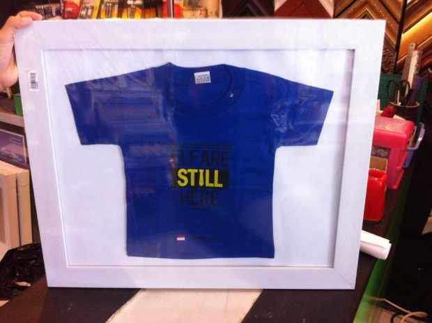 "Kaos mini ""ELF ARE STILL HERE"" Blue version, dibingkai rapi di dalam frame"